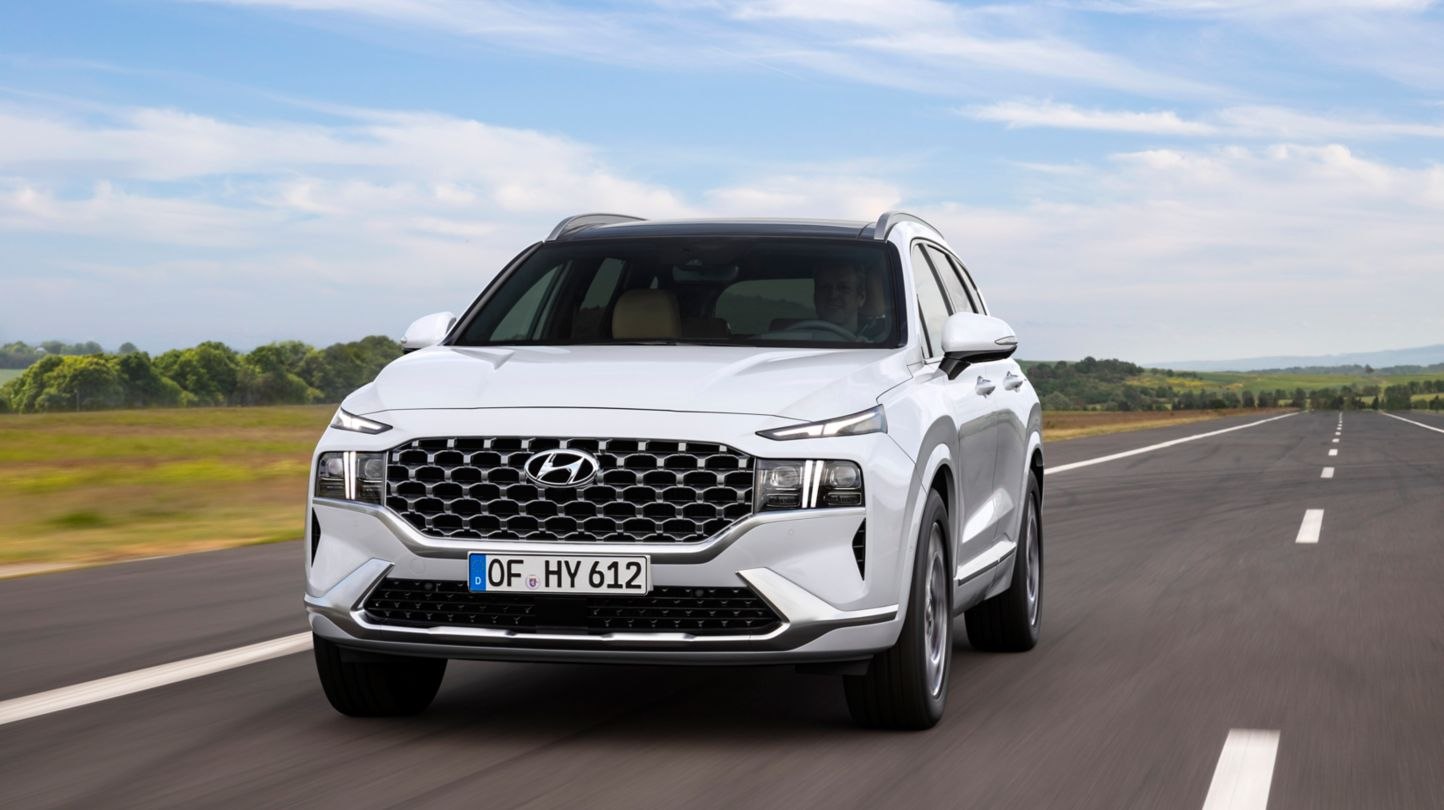 An image of the new Hyundai Santa Fe SUV from the front driving down a highway.