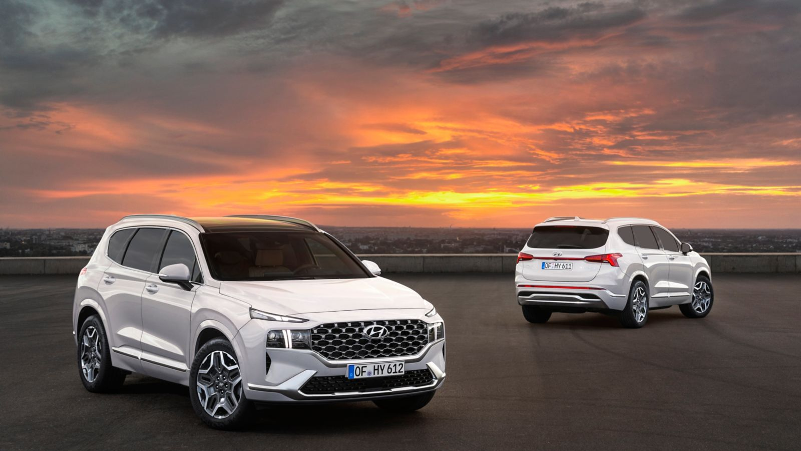 Two new Hyundai Santa Fe SUVs picture at sunset from the front and rear.
