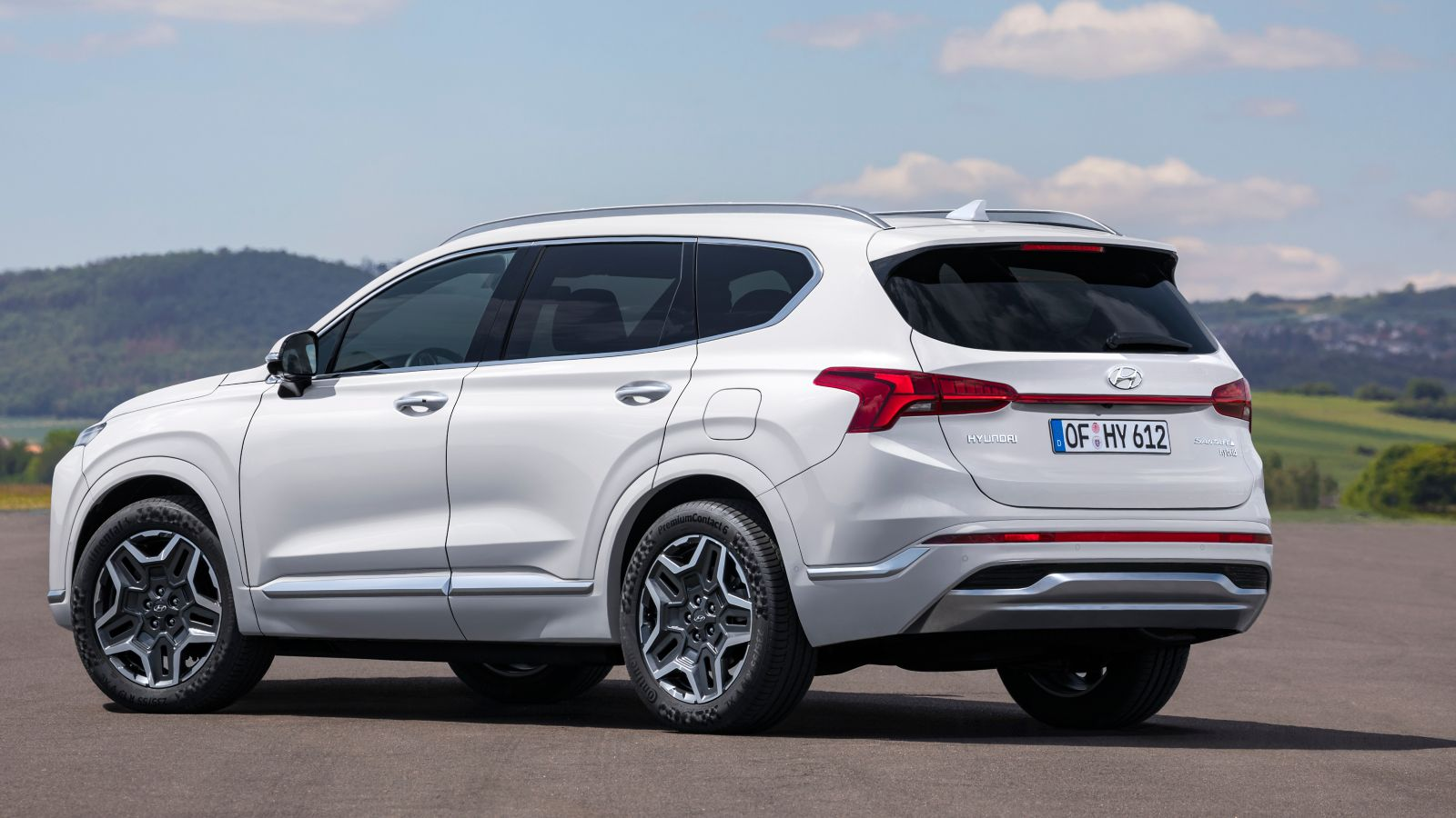 The new Hyundai Santa Fe SUV pictured from the side, parked on a country road.